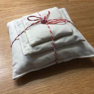 Zakjes van ongebleek katoen gevuld met bonen, zand en rijst van Speelbelovend. Samen gebonden met een rod met wit touwtje
