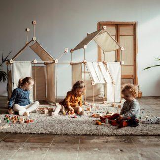 Huisjes gebouwd met Trígonos Large Kernel en Family van ongebleekt organisch katoen en drie kinderen die ervoor spelen
