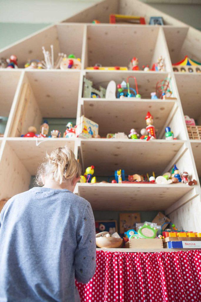 Meisje voor de houten kast vol opgeknapt houten speelgoed